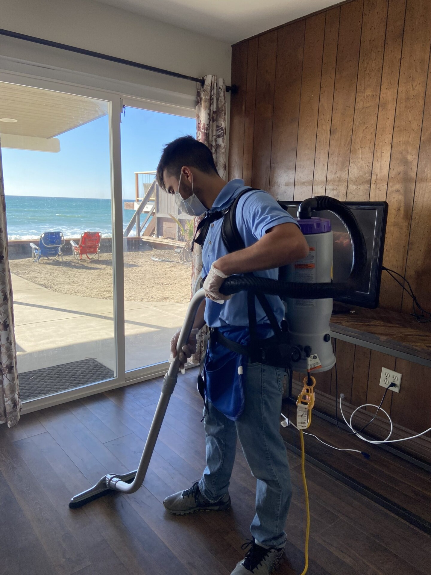 A Germicidal Maids employee hard at work using a specialized vacuum to prepare for a VRBO cleaning